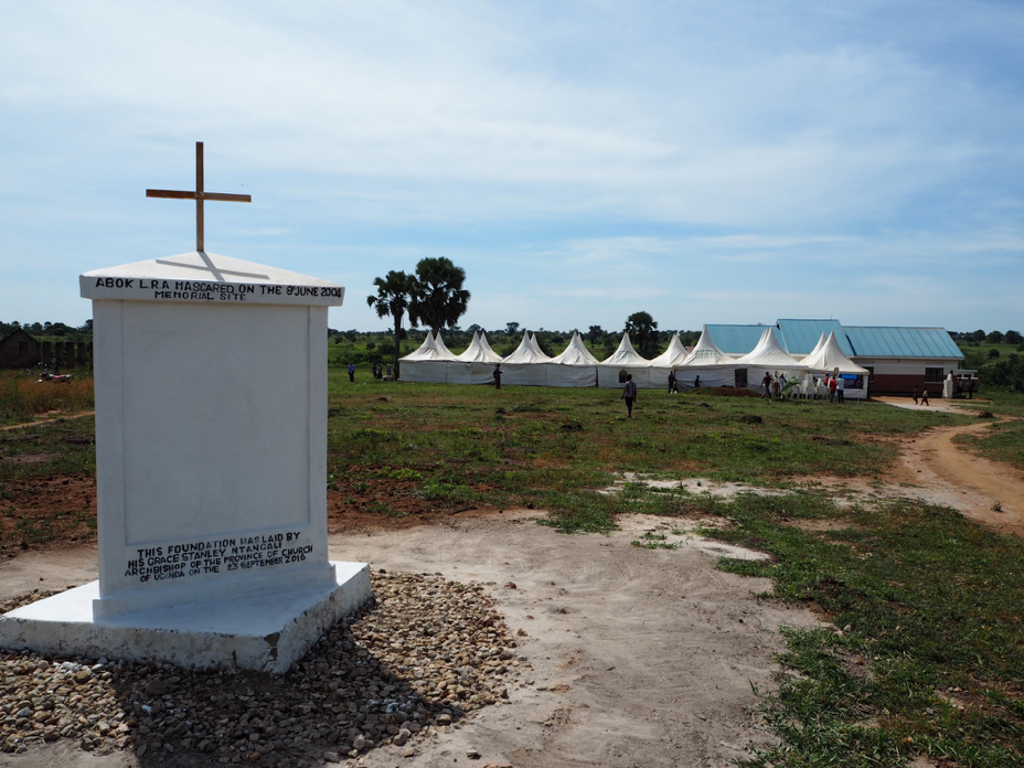 The massacre memorial in Abok, Northern Uganda. In the background: the tents for the public screening of the Ongwen trial (image: Jonas Bens).