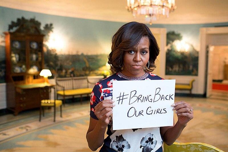 First Lady Michelle Obama präsentiert ein Schild mit dem Hashtag #BringBackOurGirls zur Unterstützung der von Boko Haram entführten nigerianischen Schülerinnen. Veröffentlicht am 7. Mai 2014 auf dem offiziellen FLOTUS-Twitter-Account. Public Domain, https://commons.wikimedia.org/wiki/File:Michelle-obama-bringbackourgirls.jpg